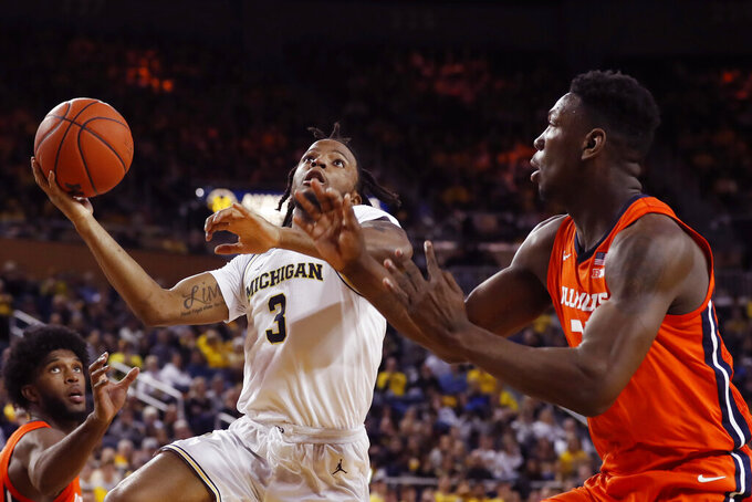 Michigan guard Zavier Simpson (3) attempts a layup as Illinois center Kofi Cockburn (21) defends during the second half of an NCAA college basketball game, Saturday, Jan. 25, 2020, in Ann Arbor, Mich. (AP Photo/Carlos Osorio)