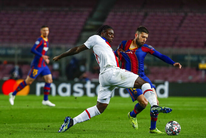 Barcelona's Jordi Alba, right, fights for the ball with PSG's Moise Kean15 during the Champions League round of 16, first leg soccer match between FC Barcelona and Paris Saint-Germain at the Camp Nou stadium in Barcelona, Spain, Tuesday, Feb. 16, 2021. (AP Photo/Joan Monfort)