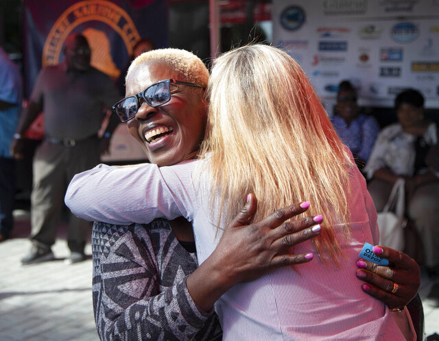 In this Wednesday, Feb. 19, 2019, Geletha Archer receives a hug from Catherine Morse after she was picked to receive a vehicle at Ed Morse Automotive Group headquarters in Delray Beach, Fla. Cabbies who live in the Abacos in Bahamas who were affected by Hurricane Dorian applied for a program in which they get $14,000 toward a new car that they can use as a taxi in the Bahamas. Forty-five Bahamians applied for vehicles. The Stuart Sailfish Club Foundation reviewed the applications and chose ten to receive vehicles. (Allen Eyestone/The Palm Beach Post via AP)