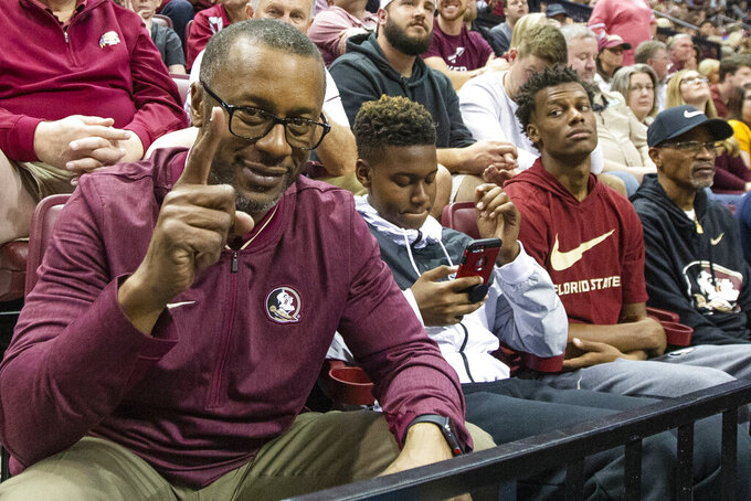 FILE - In this Jan. 12, 2019, file photo, then-Florida State head football coach Willie Taggart watches an NCAA college basketball game with his son's Jackson and Willie, Jr. in Tallahassee, Fla. Florida Atlantic announced that quarterback Willie Taggart Jr. signed with the Owls on Wednesday, Feb. 5, 2020, meaning he will play for his father, the new FAU coach. (AP Photo/Mark Wallheiser, File)