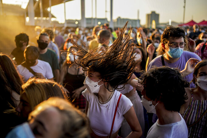 People dance during the Cruilla music festival in Barcelona, Spain, Friday, July 9, 2021. (AP Photo/Joan Mateu)