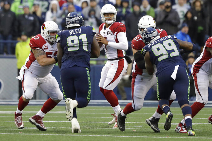 Arizona Cardinals quarterback Brett Hundley, center, drops to pass against the Seattle Seahawks during the second half of an NFL football game, Sunday, Dec. 22, 2019, in Seattle. (AP Photo/Elaine Thompson)
