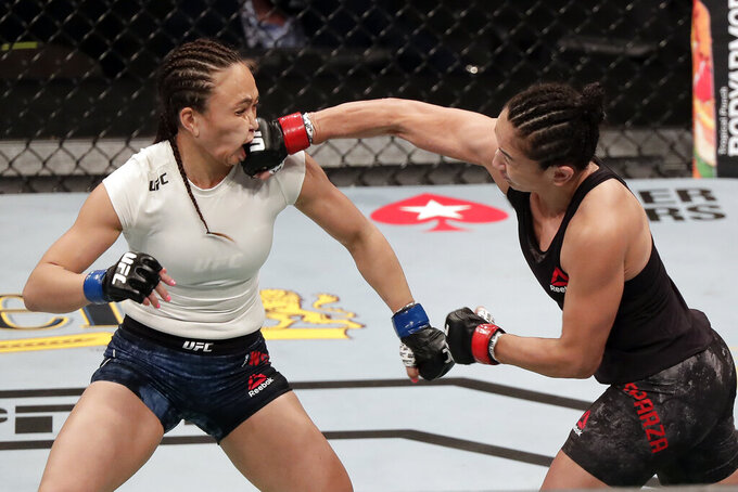 Carla Esparza, right, lands a punch on Michelle Waterson during a UFC 249 mixed martial arts bout, Saturday, May 9, 2020, in Jacksonville, Fla. (AP Photo/John Raoux)