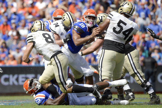 Vanderbilt quarterback Ken Seals (8) is sacked by Florida linebacker Antwuan Powell (52) during the second half of an NCAA college football game, Saturday, Oct. 9, 2021, in Gainesville, Fla. (AP Photo/Phelan M. Ebenhack)
