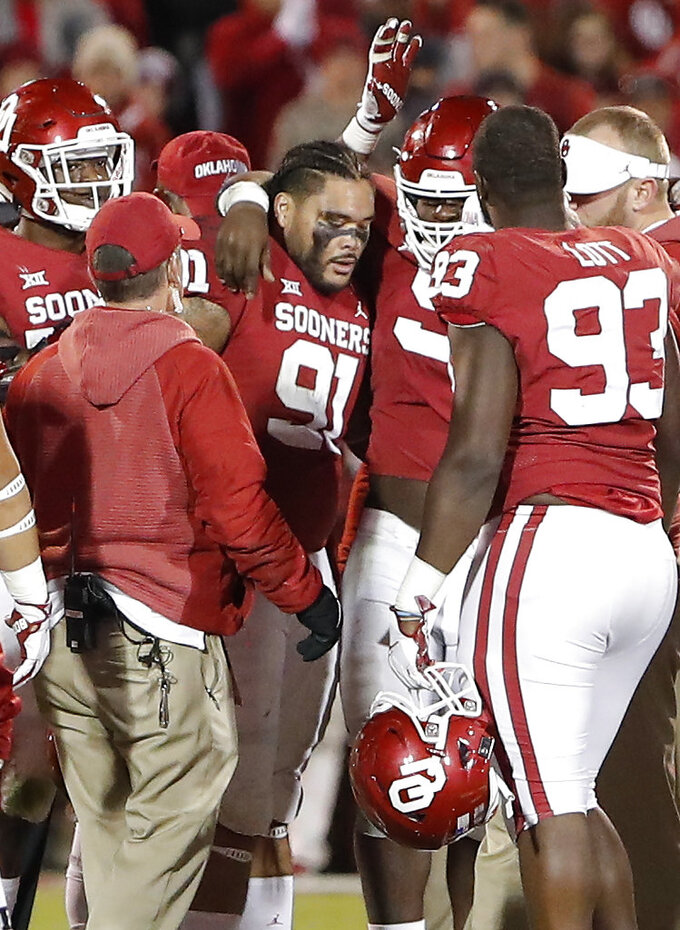 Oklahoma defensive tackle Dillon Faamatau (91) is helped off the field after a play against Oklahoma State in the second half of an NCAA college football game in Norman, Okla., Saturday, Nov. 10, 2018. Oklahoma won 48-47. (AP Photo/Alonzo Adams)