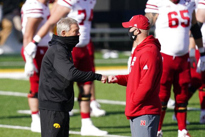Iowa head coach Kirk Ferentz, left, greets Nebraska head coach Scott Frost before an NCAA college football game, Friday, Nov. 27, 2020, in Iowa City, Iowa. (AP Photo/Charlie Neibergall)