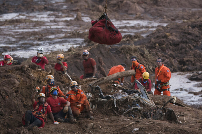 FILE - In this Jan. 28, 2019 file photo, firefighters watch the body of a person they pulled from the mud, as it is lifted up and taken away by a helicopter days after a dam collapse in Brumadinho, Brazil. A company-commissioned study released Thursday, Dec. 12, found that none of the structure's monitoring systems gave warning of the collapse that killed at least 257 people, though other experts have said the disaster could have been prevented. (AP Photo/Leo Correa, File)