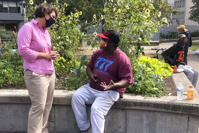 Kentucky U.S. Senate candidate Democrat Amy McGrath, speaks to a man in Jefferson Square, Thursday, Sept. 24, 2020, in Louisville, Ky. McGrath called for fundamental change to combat
