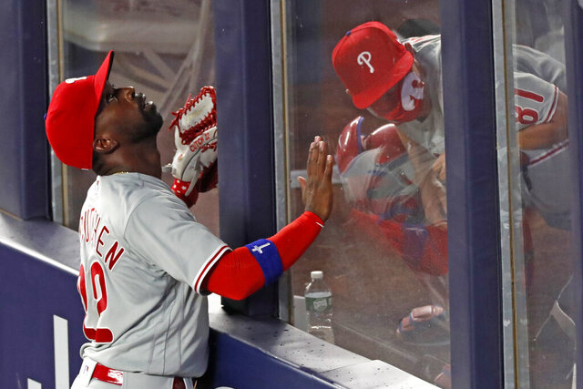 Philadelphia Phillies left fielder Andrew McCutchen (22) tracks the path of Gio Urshela's sixth-inning, three-run home run as Phillies catrching coach Greg Brodzinski ducks in the bullpen in a baseball game against the New York Yankees, Monday, Aug. 3, 2020, at Yankee Stadium in New York. (AP Photo/Kathy Willens)