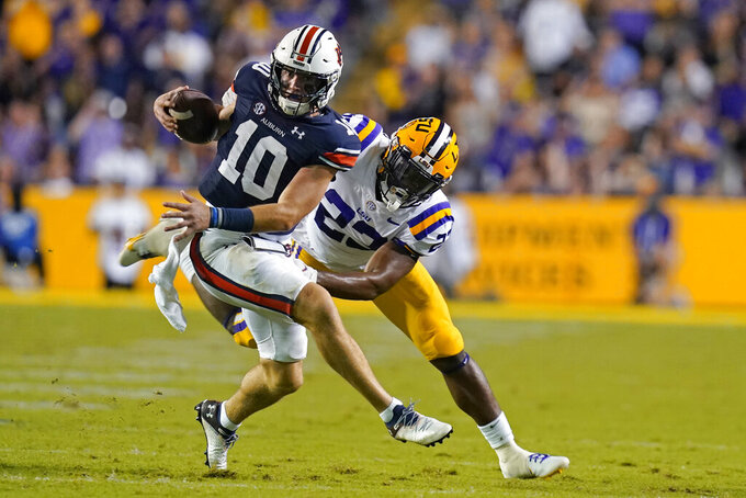 Auburn quarterback Bo Nix (10) scrambles to avoid LSU linebacker Micah Baskerville, on a play where he threw a touchdown pass, in the first half of an NCAA college football game in Baton Rouge, La., Saturday, Oct. 2, 2021. (AP Photo/Gerald Herbert)