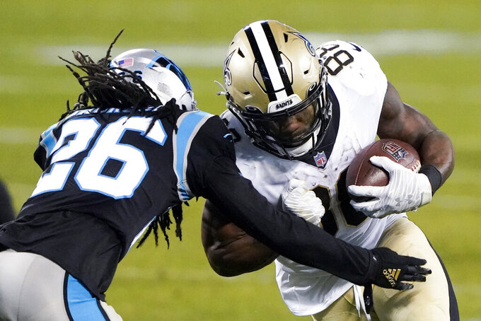 New Orleans Saints running back Ty Montgomery, right, is tackled by Carolina Panthers cornerback Donte Jackson during the second half of an NFL football game Sunday, Jan. 3, 2021, in Charlotte, N.C. (AP Photo/Brian Blanco)