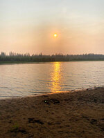 In this handout photo taken Tuesday, June 23, 2020 and provided by Olga Burtseva, a beach on the bank of Yana river is empty due to hot weather, during sunset outside Verkhoyansk, the Sakha Republic, about 4660 kilometers (2900 miles) northeast of Moscow, Russia. A record-breaking temperature of 38 degrees Celsius (100.4 degrees Fahrenheit) was registered in the Arctic town of Verkhoyansk on Saturday, June 20 in a prolonged heatwave that has alarmed scientists around the world. (Olga Burtseva via AP)