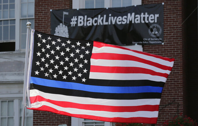 FILE - In this July 28, 2016, file photo, a flag with a blue and black stripes in support of law enforcement officers, flies at a protest by police and their supporters outside Somerville City Hall in Somerville, Mass.   An Oregon county has agreed to pay $100,000 to a black employee who sued after a co-worker pinned up a