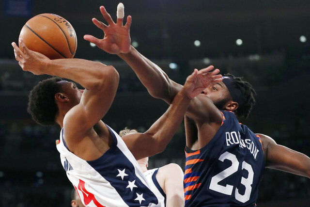 New York Knicks center Mitchell Robinson (23) defends against Washington Wizards guard Ish Smith (14) during the first half of an NBA basketball game in New York, Monday, Dec. 23, 2019. (AP Photo/Kathy Willens)