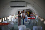 """Palestinians visit the interior of a Boeing 707 after it was converted to a cafe restaurant, in Wadi Al-Badhan, near the West Bank city of Nablus, Wednesday, Aug. 11, 2021. The Palestinian territory has no civilian airport and those who can afford a plane ticket must catch their flights in neighboring Jordan. After a quarter century of effort, twins brothers, Khamis al-Sairafi and Ata, opened the """"Palestinian-Jordanian Airline Restaurant and Coffee Shop al-Sairafi"""" on July 21, 2021, offering people an old airplane for customers to board. (AP Photo/Majdi Mohammed)"""