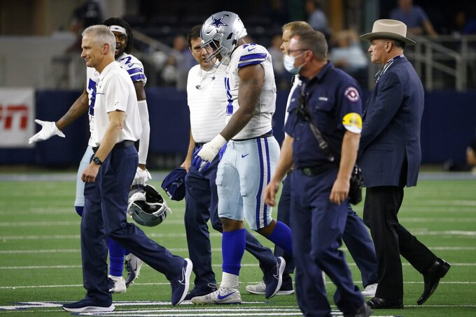Dallas Cowboys linebacker Micah Parsons (11) is escorted off the field after being attended to by team staff in the second half of an NFL football game against the Philadelphia Eagles in Arlington, Texas, Monday, Sept. 27, 2021. (AP Photo/Ron Jenkins)