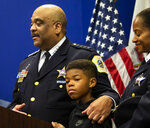 Chicago Police Department Supt. Eddie Johnson puts his arm around his 10-year-old son as he announces his retirement during a press conference at CPD headquarters, Thursday morning, Nov. 7, 2019. (Ashlee Rezin Garcia/Chicago Sun-Times via AP)