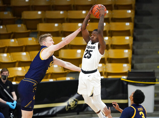 Colorado guard McKinley Wright IV, center, pulls in a rebound between California guards Ryan Betley, left, and Jarred Hyder in the first half of an NCAA college basketball game Thursday, Jan. 14, 2021, in Boulder, Colo. (AP Photo/David Zalubowski)
