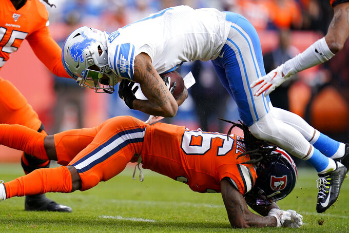 Detroit Lions wide receiver Kenny Golladay is tackled by Denver Broncos defensive back Trey Marshall, bottom, during the first half of an NFL football game, Sunday, Dec. 22, 2019, in Denver. (AP Photo/Jack Dempsey)