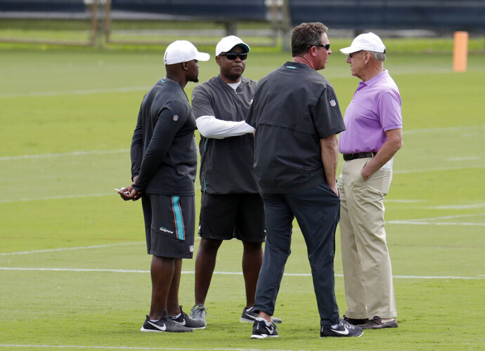 Miami Dolphins head coach Brian Flores, left, general manager Chris Grier, second from left, former quarterback Dan Marino, and owner Stephen Ross, right, talk on the field during voluntary minicamp at the Miami Dolphins NFL football training facility, Wednesday, April 17, 2019, in Davie, Fla. (AP Photo/Lynne Sladky)