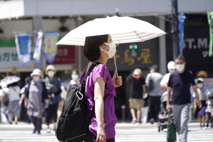 """A woman wearing a face mask to curb the spread of the coronavirus walks with a parasol on a street in Tokyo Thursday, Aug. 5, 2021. Japan is playing host to the Tokyo Olympics. But the capital, as well as other populous areas, are in the middle of a government-declared """"state of emergency"""" to curb surging COVID-19 infections. (AP Photo/Kantaro Komiya)"""