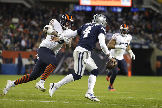 Dallas Cowboys quarterback Dak Prescott (4) is chased by Chicago Bears' Aaron Lynch (99) during the second half of an NFL football game, Thursday, Dec. 5, 2019, in Chicago. Chicago won 31-24. (AP Photo/Morry Gash)
