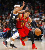FILE - In this March 31, 2019, file photo, Atlanta Hawks guard Trae Young (11) drives to the basket as Milwaukee Bucks guard Tim Frazier (12) defends in overtime of an NBA basketball game, in Atlanta. With a pair of picks in the top 10 — or perhaps a single selection that's higher than what they have now, should they work out a trade — the Hawks can add to a pair of gems from the last two drafts, Trae Young and John Collins. (AP Photo/Todd Kirkland, File)