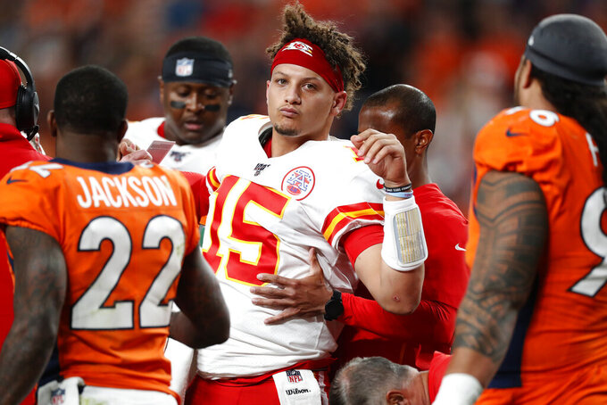 Kansas City Chiefs quarterback Patrick Mahomes (15) is helped off the field after being injured against the Denver Broncos during the first half of an NFL football game, Thursday, Oct. 17, 2019, in Denver. (AP Photo/David Zalubowski)