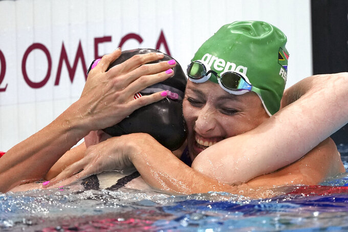 Gold medalist Lydia Jacoby of the United States, left, is embraced by silver medalist Tatjana Schoenmaker of South Africa after winning the final of the women's 100-meter breaststroke at the 2020 Summer Olympics, Tuesday, July 27, 2021, in Tokyo, Japan. (AP Photo/Matthias Schrader)