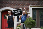 Henry Webber, right, and Christine Jacobs wave from their front steps as protesters pass their home on a private street Friday, July 3, 2020, in St. Louis. The couple live not far from Mark and Patricia McCloskey who were seen on the front lawn of their mansion with weapons drawn on June 28, 2020, while confronting passing protesters. Webber said he wanted to send a different message to the protesters. (AP Photo/Jeff Roberson)