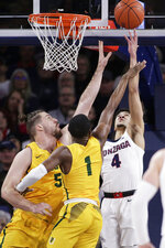 Gonzaga guard Ryan Woolridge (4) shoots while pressured by San Francisco center Jimbo Lull (5) and guard Jamaree Bouyea (1) during the first half of an NCAA college basketball game in Spokane, Wash., Thursday, Feb. 20, 2020. (AP Photo/Young Kwak)