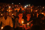 FILE - In this Sunday, April 7, 2019 file photo, Rwandans sitting in the stands hold candles as part of a candlelit vigil during a genocide memorial service held at Amahoro stadium in the capital Kigali, Rwanda. Felicien Kabuga, one of the most wanted fugitives in Rwanda's 1994 genocide who had a $5 million bounty on his head, has been arrested in Paris, authorities said Saturday, May 16, 2020. (AP Photo/Ben Curtis, File)