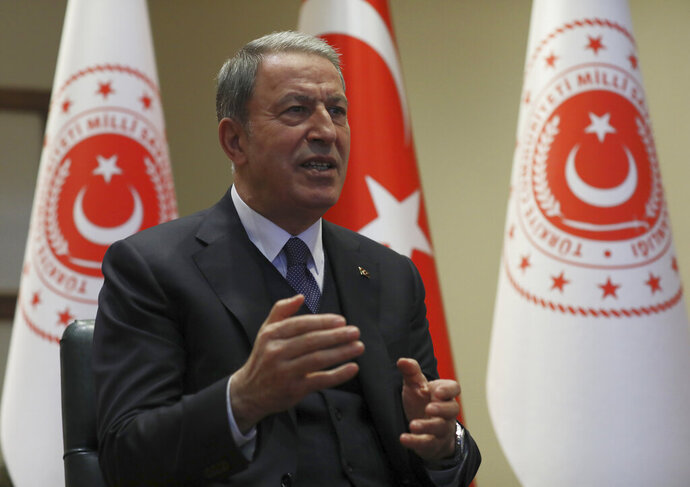 Turkey's Defense Minister Hulusi Akar speaks during an interview with the Associated Press, in Ankara, Turkey, Tuesday, Feb. 11, 2020. Akar said as many as four observation posts and two military positions are now in Syrian-controlled territory as the Syrian forces continued their advance into northwestern Idlib province, the last rebel stronghold and warned Turkish soldiers were under orders to retaliate forcefully to attacks on the military posts.(AP Photo/Burhan Ozbilici)