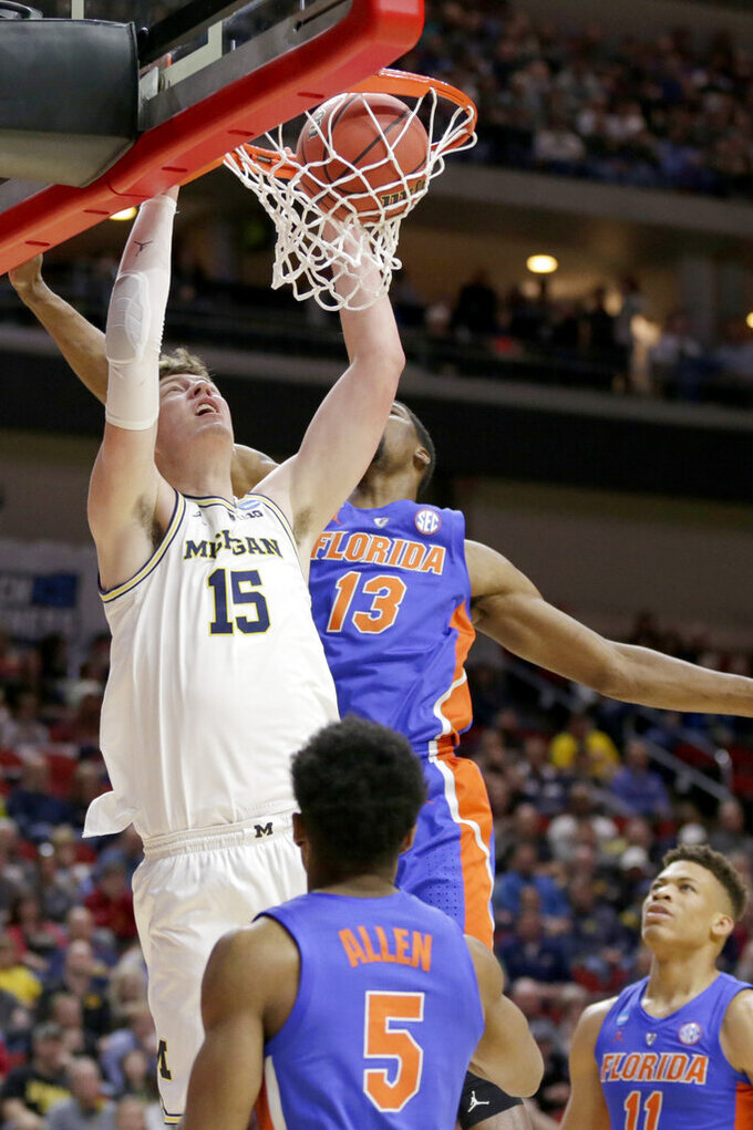 Michigan's Jon Teske (15) dunks over Florida's KeVaughn Allen (5) and Kevarrius Hayes (13) during the first half of a second round men's college basketball game in the NCAA Tournament, in Des Moines, Iowa, Saturday, March 23, 2019. (AP Photo/Nati Harnik)