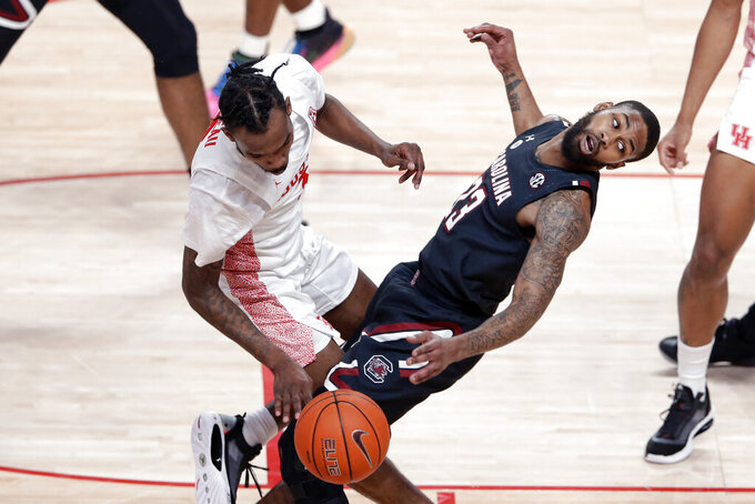 Houston guard DeJon Jarreau, left, draws a foul as he charges into South Carolina guard Seventh Woods (23) during the first half of an NCAA college basketball game Saturday, Dec. 5, 2020, in Houston. (AP Photo/Michael Wyke)