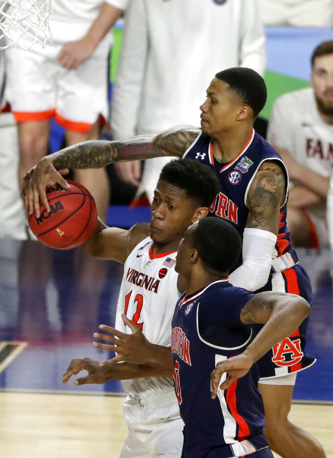 Virginia's De'Andre Hunter (12) battles for a loose ball against Auburn's J'Von McCormick and Horace Spencer (0) during the second half in the semifinals of the Final Four NCAA college basketball tournament, Saturday, April 6, 2019, in Minneapolis. (AP Photo/Matt York)