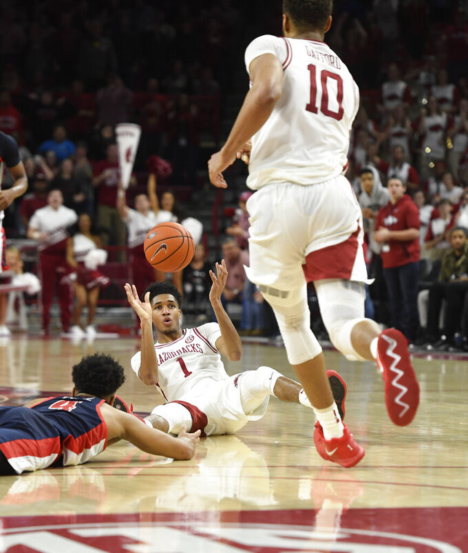 Arkansas guard Isaiah Joe (1) tries to get the ball to teammate Daniel Gafford (10) as Mississippi defender Breein Tyree (4) falls to the ground during the second half of an NCAA college basketball game, Saturday, March 2, 2019 in Fayetteville, Ark. (AP Photo/Michael Woods)