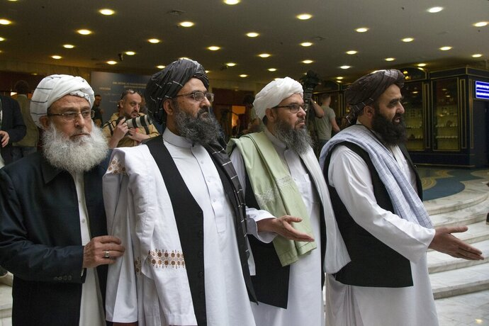 FILE - In this May 28, 2019, file photo, Mullah Abdul Ghani Baradar, the Taliban group's top political leader, second left, arrives with other members of the Taliban delegation for talks in Moscow, Russia. U.S. peace envoy Zalmay Khalilzad held on Saturday, Dec. 7, 2019 the first official talks with Afghanistan's Taliban since last September when President Donald Trump declared a near-certain peace deal with the insurgents dead. (AP Photo/Alexander Zemlianichenko, File)