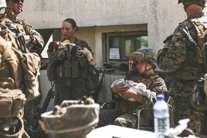 In this Aug. 20, 2021, image provided by the U.S. Marine Corps, Marines assigned to the 24th Marine Expeditionary Unit (MEU), including Sgt. Nicole Gee, standing at left, calm infants during an evacuation at Hamid Karzai International Airport in Kabul, Afghanistan. Officials said Aug. 28, that Gee of Sacramento, Calif., was one of the Marines killed in Thursday's bombing at the airport. (Sgt. Isaiah Campbell/U.S. Marine Corps via AP)