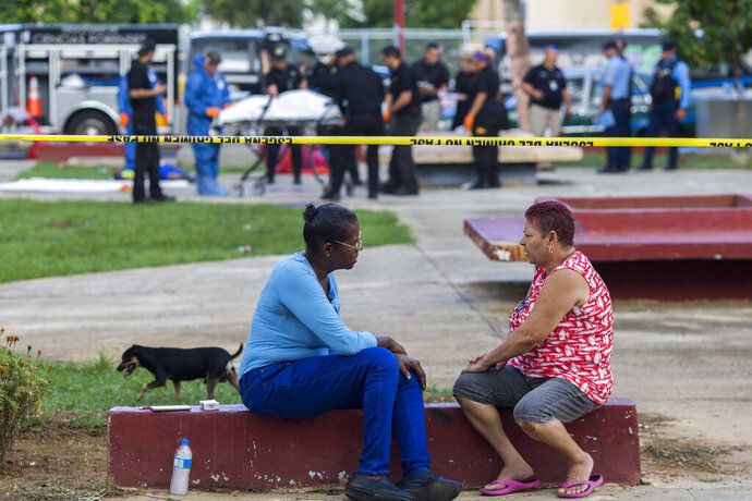 A couple of neighbors talk next to a strand of police tape as investigators in the background recover the bodies at the scene of a multiple killing in San Juan, Puerto Rico, Tuesday, Oct. 15, 2019. Several people are reported dead following a shooting in the Rio Piedras neighborhood of San Juan. (AP Photo/Dennis M. Rivera Pichardo)