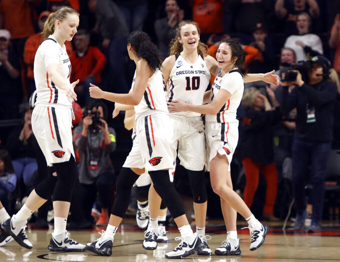 From left to right, Oregon State's Joanna Grymek, Taya Corosdale, Katie McWilliams and Aleah Goodman (1) celebrate their win over Boise State in a first-round game of the NCAA women's college basketball tournament in Corvallis, Ore., Saturday, March 23, 2019. (AP Photo/Amanda Loman)