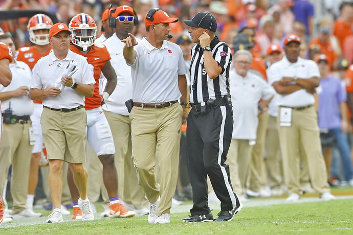 Clemson head coach Dabo Swinney, center, discusses a call with an official during the first half of an NCAA college football game against Florida State Saturday, Oct. 12, 2019, in Clemson, S.C. (AP Photo/Richard Shiro)