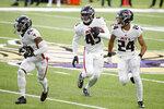 Atlanta Falcons linebacker Deion Jones, center, returns an interception with teammates Kendall Sheffield, left, and A.J. Terrell, right, during the first half of an NFL football game against the Minnesota Vikings, Sunday, Oct. 18, 2020, in Minneapolis. (AP Photo/Bruce Kluckhohn)