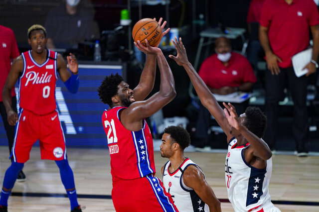 Philadelphia 76ers center Joel Embiid (21) shoots over Washington Wizards center Thomas Bryant (13) during the second half of an NBA basketball game Wednesday, Aug. 5, 2020 in Lake Buena Vista, Fla. (AP Photo/Ashley Landis)