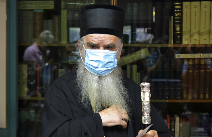 FILE - In this Sunday, Aug. 30, 2020. file photo, Bishop Amfilohije wearing a mask against the spread of COVID-19, prepares to vote in parliamentary elections at a polling station in Cetinje, some 30 km south of Podgorica, Montenegro. Amfilohije, the head of the Serbian Orthodox Church in Montenegro, which led months of protests against the small Balkan state's pro-Western government, has died in hospital after contracting the coronavirus, the church said Friday, Oct. 30, 2020. (AP Photo/Risto Bozovic, File)