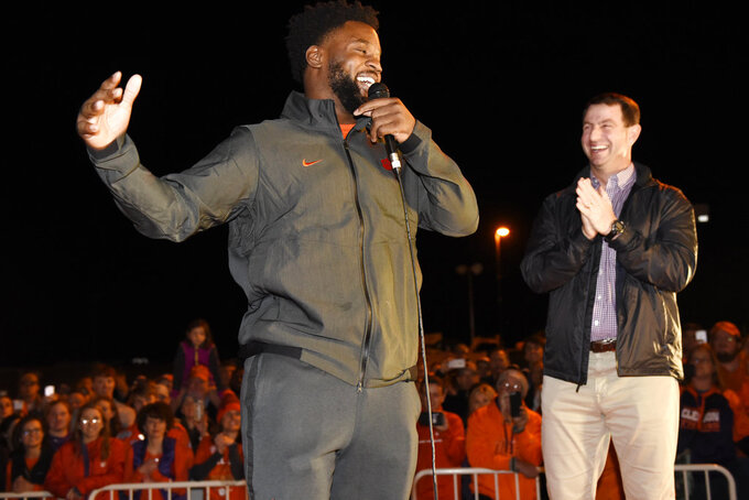 Clemson's Christian Wilkins, left, and coach Dabo Swinney laugh after the Clemson football team returned to campus Tuesday, Jan. 8, 2019, in Clemson, S.C., the day after the Tigers defeated Alabama 44-16 in the College Football Playoff championship game. (AP Photo/Richard Shiro)