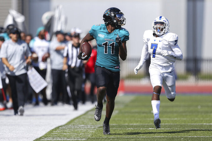 Coastal Carolina wide receiver Kameron Brown (11) runs along the sideline chased by Buffalo safety E.J. Brown (7) after a catch during the second half of a NCAA college football game in Buffalo, N.Y. on Saturday, Sept. 18, 2021. (AP Photo/Joshua Bessex)
