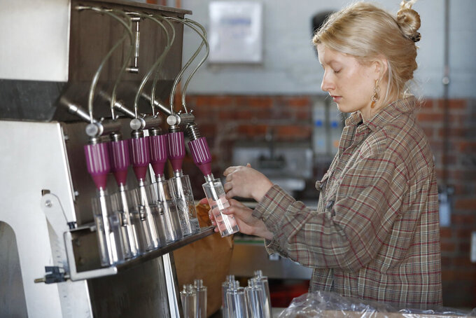 Two James Spirits employee Allie Sieracki fills bottles with hand sanitizer being produced at the distillery, Friday, April 3, 2020, in Detroit. After a revision to FDA regulations on the manufacture of hand sanitizer, bars and alcohol producers are permitted to distribute the product. The distillery is one of many across the country which have shifted their production away from spirits and starting to make hand sanitizer to help ease the coronavirus-induced shortage of the product. (AP Photo/Carlos Osorio)