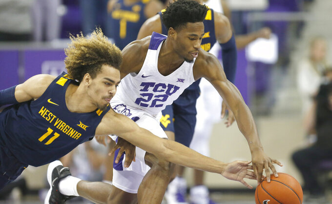 West Virginia forward Emmitt Matthews (11) attempts to steal the ball from TCU guard RJ Nembhard (22) during the first half of an NCAA college basketball game, Saturday, Feb. 22, 2020 in Fort Worth, Texas. (AP Photo/Ron Jenkins)