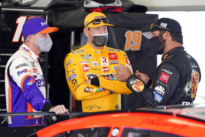 Denny Hamlin, left, Kyle Busch, center and Martin Truex Jr. talk in a garage before the start of a NASCAR Daytona 500 auto race practice session at Daytona International Speedway, Wednesday, Feb. 10, 2021, in Daytona Beach, Fla. (AP Photo/John Raoux)